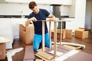 Man assembling furniture in his new home